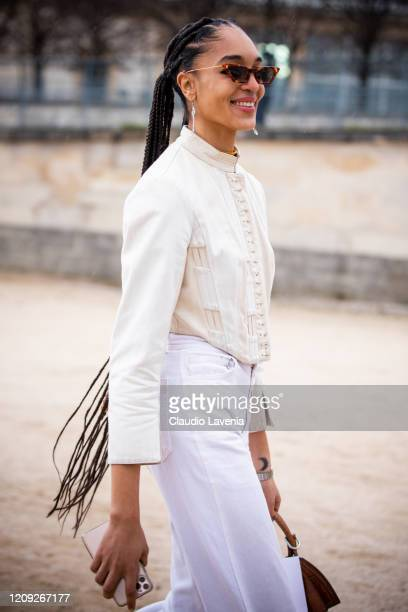 Model Indira Scott, wearing a cream top and white pants,, is seen outside Dior, during Paris Fashion Week - Womenswear Fall/Winter 2020/2021 : Day...