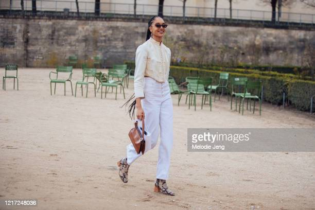 Model Indira Scott wears a cat-eye sunglasses, vintage-style cream button-up top , white jeans, a small brown bag, and python boots after the Dior...