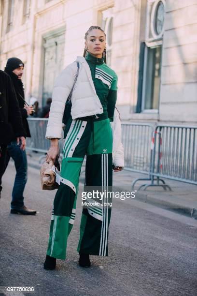 Model Indira Scott wears a green Adidas jumpsuit and cropped white puffer jacket after Dior during Couture SS19 Fashion Week on January 21 2019 in...