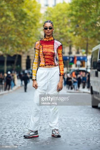 Model Indira Scott wears green sunglasses, a Asai Orange & Pink Hot Wok Turtleneck, white track pants, and gray Nike sneakers after the Altuzarra...