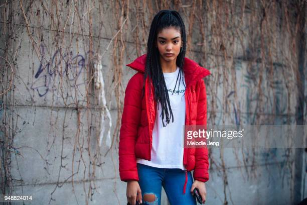 Model Ines Oussaidi wears a red jacket white tshirt and blue jeans during Milan Fashion Week Fall/Winter 2018/19 on February 24 2018 in Milan Italy