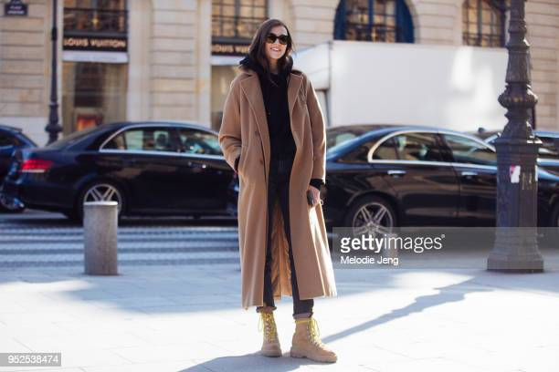Model Irina Djuranovic wears a long light brown coat black hoodie and tan boots on February 28 2018 in Paris France