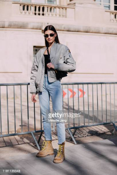 Model Irina Djuranovic wears black cateye sunglasses green bomber jacket blue jeans and light brown boots after the Unravel Project show at Grand...