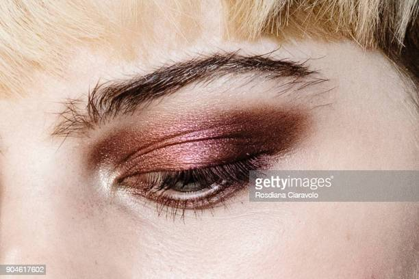 A model is is seen make up detail ahead of the Versace show during Milan Men's Fashion Week Fall/Winter 2018/19 on January 13 2018 in Milan Italy