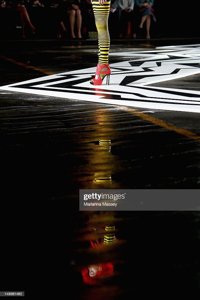 A model is reflected in water on the floor as she showcases designs by Romance Was Born on the catwalk on day one of Mercedes-Benz Fashion Week Australia Spring/Summer 2012/13 at Pier 2 on April 30, 2012 in Sydney, Australia.