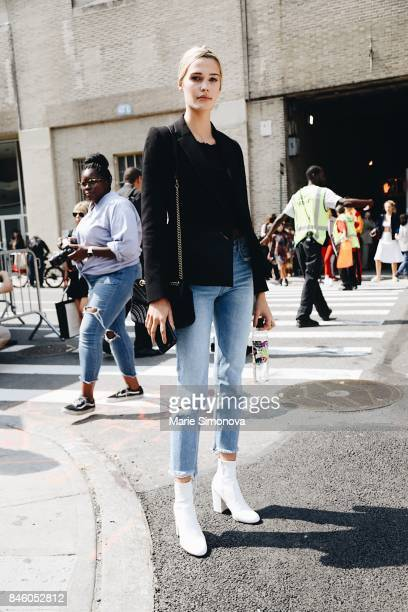 Model is seen outside Skylight Clarkson wearing black jacket black crop top blue jeans white high heels shoes and black sunglasses during New York...