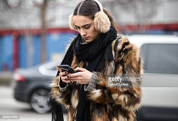 A model is seen outside the Milly show wearing a brown fur coat with pink earmuffs during New York Fashion Week Women's Fall/Winter 2016 on February...