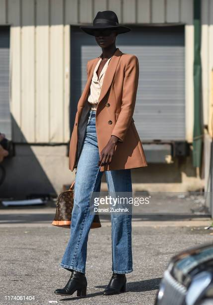 Model is seen wearing a beige jacket, cream top, blue jeans, black leather boots and black hat outside the Michael Kors show during New York Fashion...