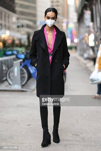Model is seen wearing a black coat, pink jacket, black pants and black shoes outside the Christian Siriano show during New York Fashion Week F/W21 on...
