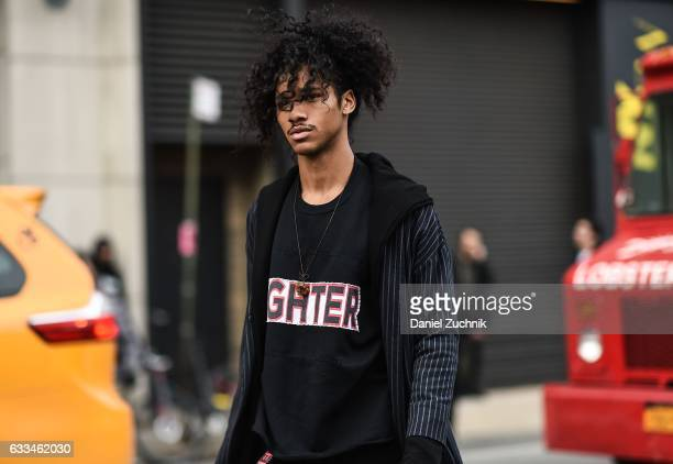 A model is seen wearing a black Fighter shirt and black and white striped coat outside of the Rochambeau show during New York Fashion Week Men's AW17...