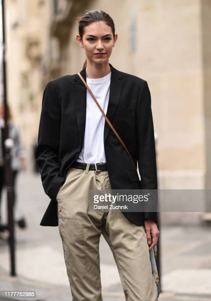 Model is seen wearing a black jacket, white top and beige pants outside the Altuzarra show during Paris Fashion Week SS20 on September 28, 2019 in...