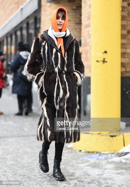 A model is seen wearing a brown and white striped fur coat and orange hoodie outside of the Tadashi Shoji show during New York Fashion Week Women's...