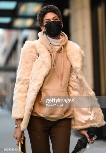 Model is seen wearing a cream coat, tan hoodie and brown pants outside the Rebecca Minkoff show during New York Fashion Week F/W21 at Spring Studios...