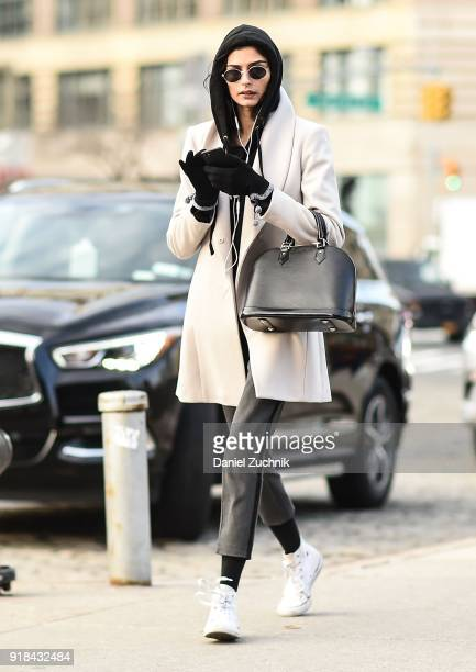 A model is seen wearing a cream jacket black hoodie and gray pants with white sneakers outside the Esteban Cortazar show during New York Fashion Week...