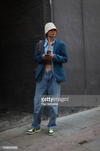 Model is seen wearing a Denim Ensemble with a Bucket Hat at Richard Quinn, during London Fashion Week September 2021 on September 21, 2021 in London,...