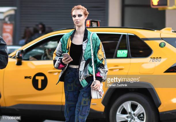 Model is seen wearing a green graphic jacket, black top, painted jeans outside the R13 show during New York Fashion Week S/S20 on September 07, 2019...