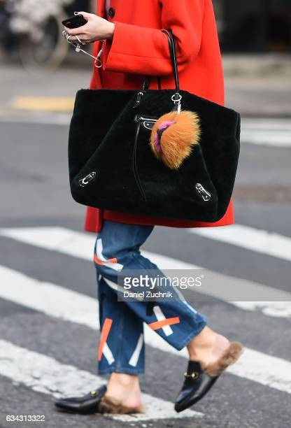 A model is seen wearing an orange coat blue painted jeans and fur shoes on the streets of Soho on February 8 2017 in New York City