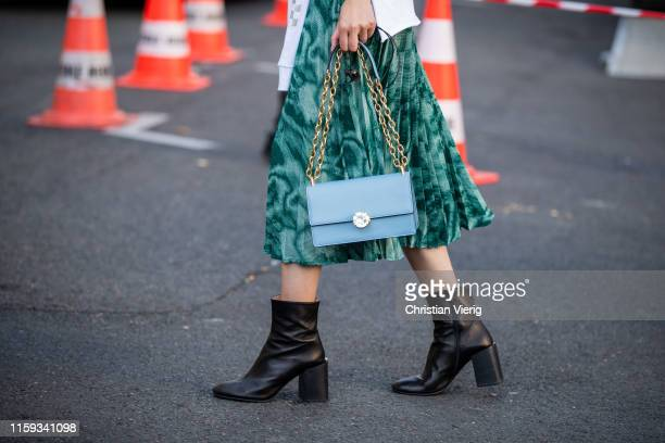 A model is seen wearing green skirt blue bag ankle boots outside Acne during Paris Fashion Week Haute Couture Fall/Winter 2019/2020 on June 30 2019...
