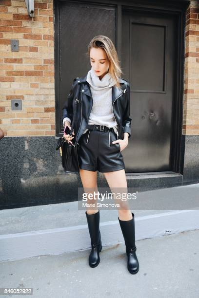 Model is seen wearing grey sweater black lether jacket and skirt during New York Fashion Week on September 11 2017 in New York City
