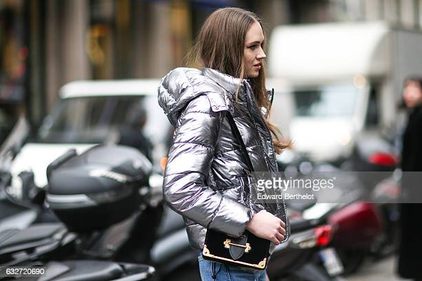 A model is wearing a silver shiny puffer coat a bag and blue denim jeans outside the Elie Saab show during Paris Fashion Week Haute Couture Spring...