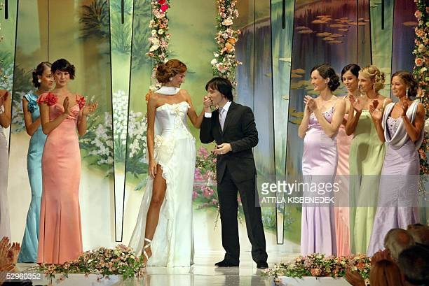 Model is welcomed with a handkiss by Hungarian designer Tamas Naray on catwalk in the Gala Hall of the Grand Hotel Royal in Budapest 20 May 2005...