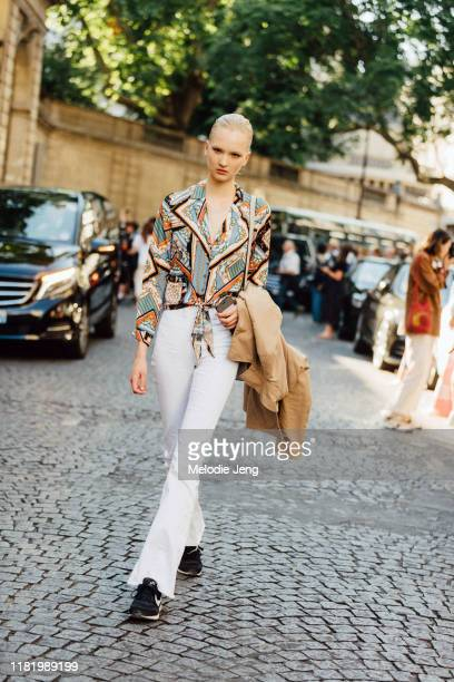 Model Isa Peerdeman wears a green print top, white pants, and black Nike sneakers after the Valentino show during Couture Fashion Week Fall/Winter...