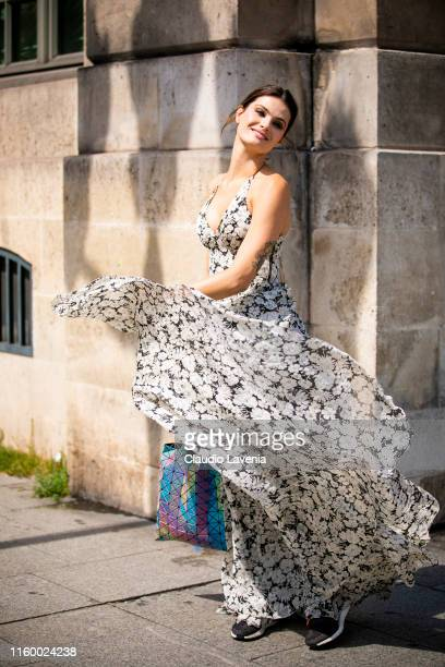 Model Isabeli Fontana wearing a holographic Issey Miyake bag and floral print maxi dress is seen outside Dundas show during Paris Fashion Week Haute...