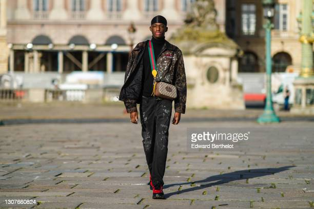 Model Issa Seck @issa_sck wears a beanie hat, a black turtleneck pullover, a necklace, a military camouflage print jacket from Dickies with the...