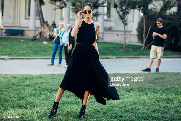 Model Izabel Goulart wears black sunglasses belted summer dress and boots after the Alberta Ferretti show during Milan Fashion Week Spring/Summer...