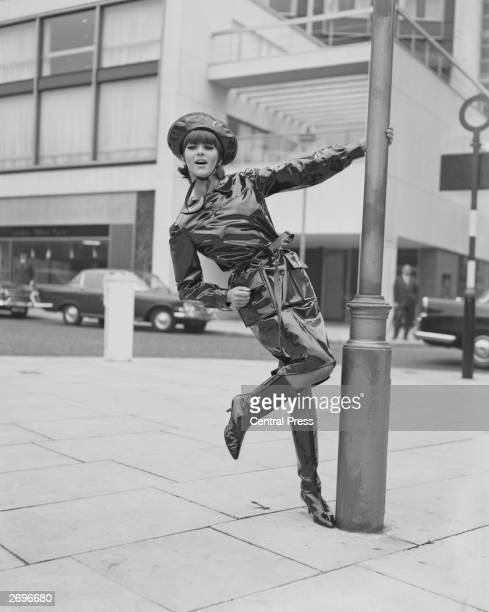 Model Jackie Bowyer swings on a lamppost wearing a black oilskin wetweather outfit from Mary Quant of matching coat and hat with shiny highheeled...