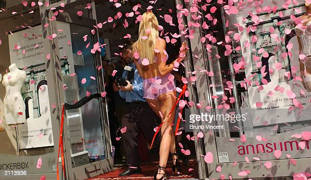 Model Jacqueline Gold stands in the entrance as confetti falls at the opening of the second Ann Summers store on Oxford Street June 26 2003 in London