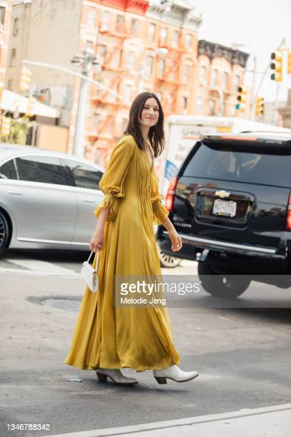 Model Jacquelyn Jablonski wears a long yellow pleated dress, white boots, and carries a small whilte purse the Khaite show on September 12, 2021 in...