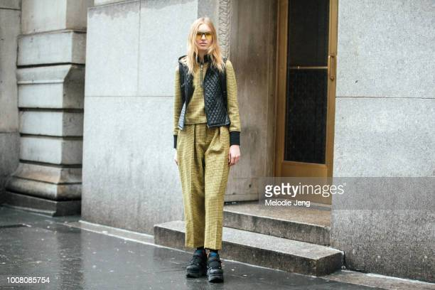 Model Jacquelyn Jablonski wears yellow sunglasses a black vest and matching 31 Phillip Lim yellow print top and pants and chunky black sneakers after...