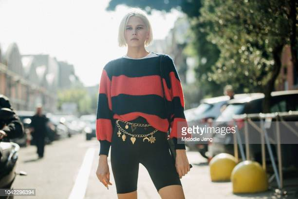 Model Jana Julius wears a black and red striped sweater black bike shorts and jewelry around her waist during Milan Fashion Week Spring/Summer 2019...