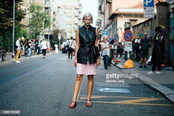 Model Jana Julius wears a black leather vest black Jil Sander purse pink dress and red sandals during Milan Fashion Week Spring/Summer 2019 on...