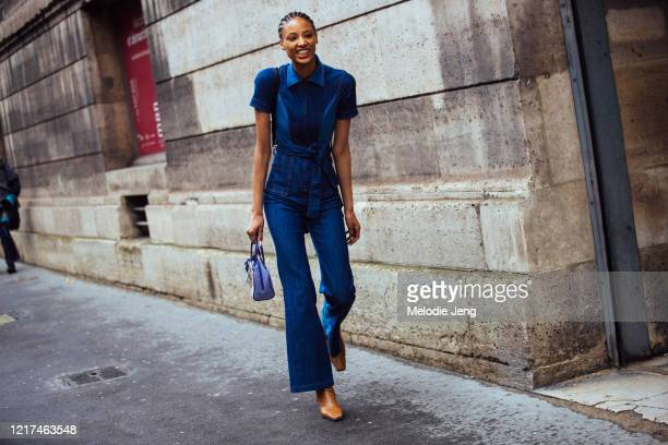 Model Janaye Furman wears a fitted denim jumpsuit, a small purple bag, and brown leather boots after the Giambattista Valli show during Paris Fashion...