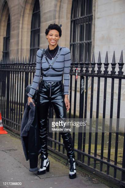 Model Janaye Furman wears a gray striped sweater, black harness, black leather pants, and black and white heels after the Paco Rabanne show during...