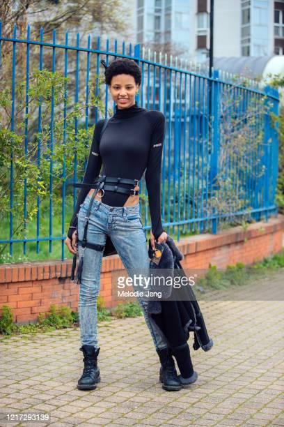 Model Janaye Furman wears an afro pick, black Prix body suit, harness belt, acid wash jeans, and black boots after the Balmain show during Paris...