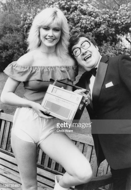 Model Janine Andrews with Northern Irish comedian Frank Carson London 9th April 1981 Andrews is holding a new Fidelity radio which recharges its...