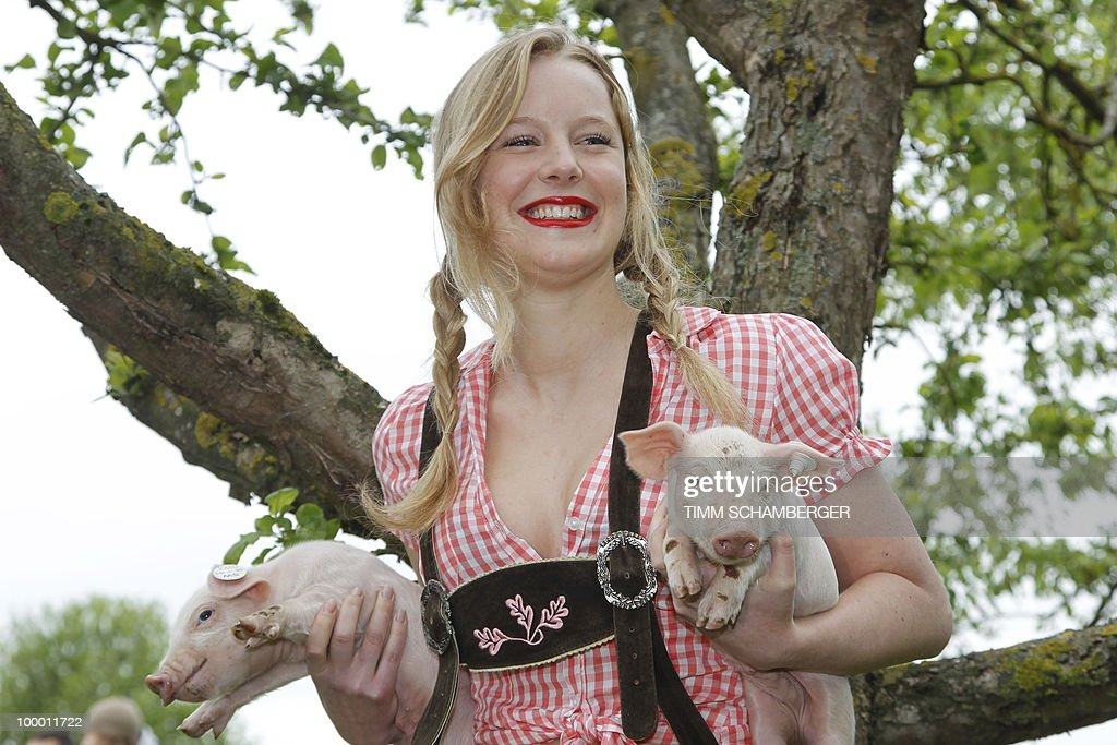 Model Jasmin poses with two piglets during a photocall to promote the 'Young Farmers Calendar 2011' on a farm in Schraudenbach, southern Germany, on May 20, 2010. More than 250 young women have applied to become one of the calendar's motives.