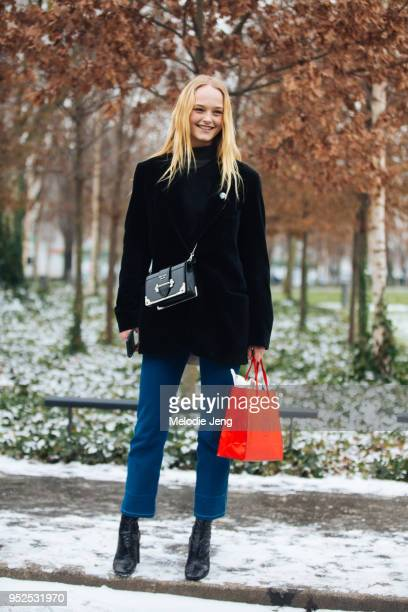 Model Jean Campbell wears a black Prada Cahier shoulder bag black jacket blue trousers and black heeled boots after the Chloe show on March 1 2018 in...
