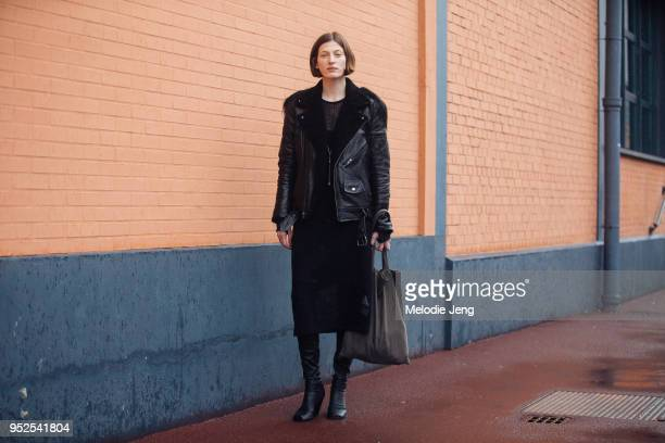 Model Jennae Quisenberry wears an all black outfit a leather jacket dress abovetheknee boots and a brown tote bag after the Balenciaga show on March...