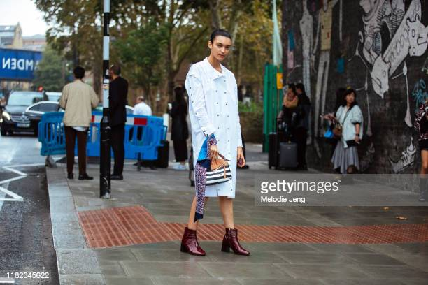 Model Jess Cole wears a white coat, striped Loewe bag, and red boots at the Christopher Kane show during London Fashion Week September 2019 on...