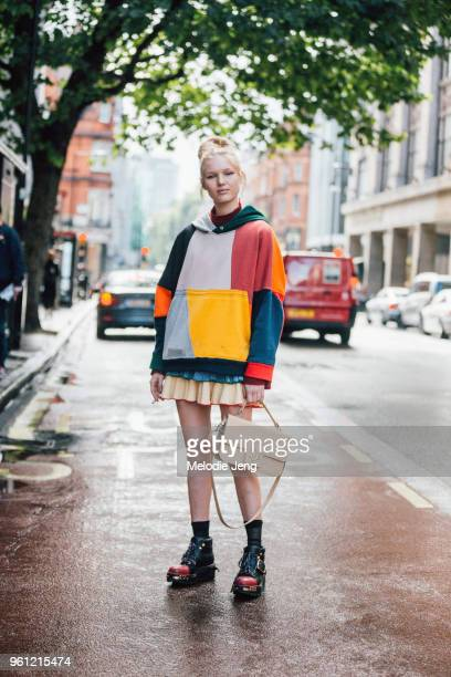 Model Jess PW wears a colorblock hoodie short skirt tan JW Anderson bag and black chunky Prada boots during London Fashion Week Spring/Summer 2018 on...