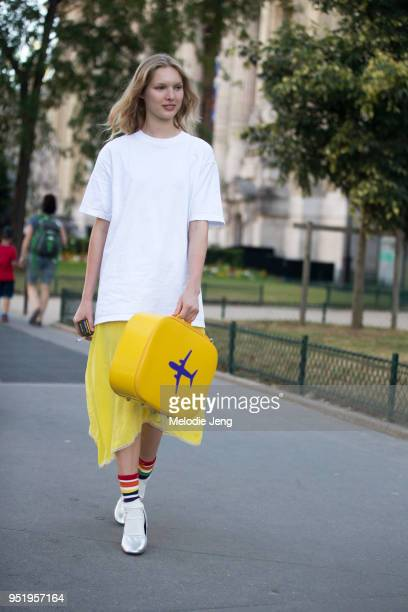 Model Jess PW wears an oversized white tshirt yellow skirt rainbow striped socks silver ballet flats and a yellow airline bag on July 03 2017 in...