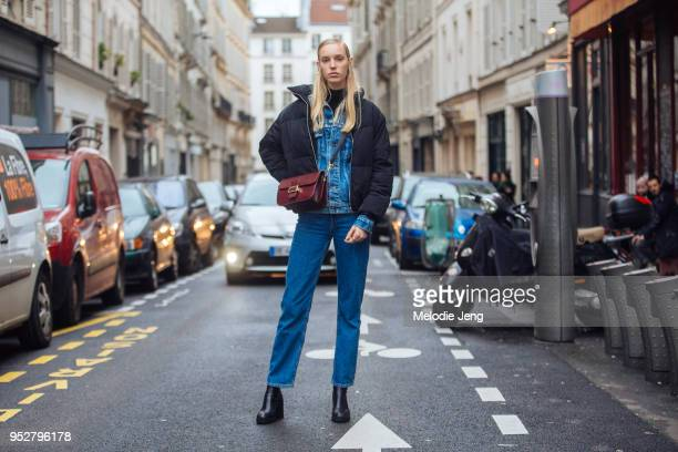 Model Jessie Bloemendaal wears a black puffer jacket maroon purse denim jacket and blue jeans and black bootson January 23 2018 in Paris France