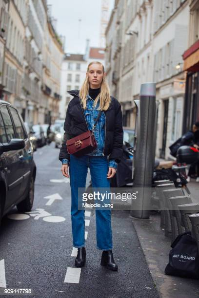 Model Jessie Bloemendaal wears a black puffer jacket over a denim jacket and jeans outside the Ellery show at Ecole des BeauxArts on January 23 2018...