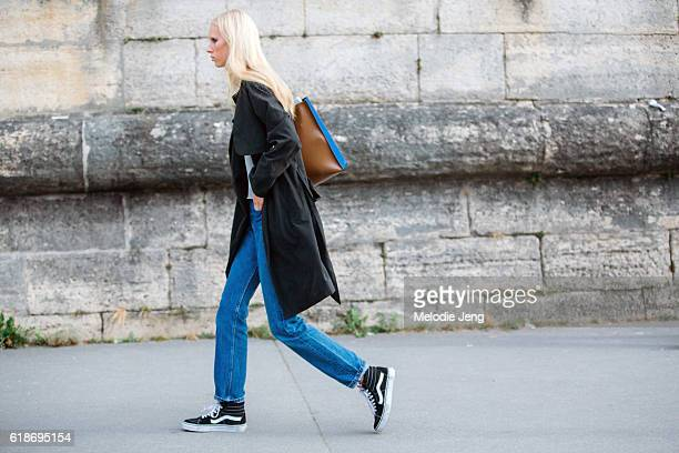 Model Jessie Bloemendaal wears a black trench coat Celine purse white top jeans and black Vans sneakers after the Elie Saab show at the Tuileries on...