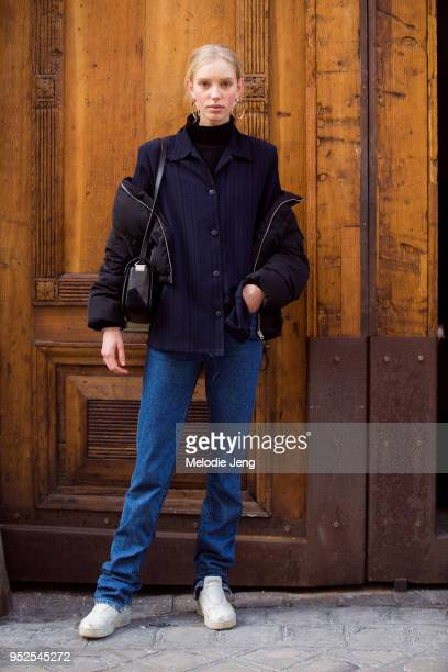 Model Jessie Bloemendaal wears a blue button shirt a black puffer jacket off her shoulders blue jeans and white Celine lowtop sneakers on March 05...