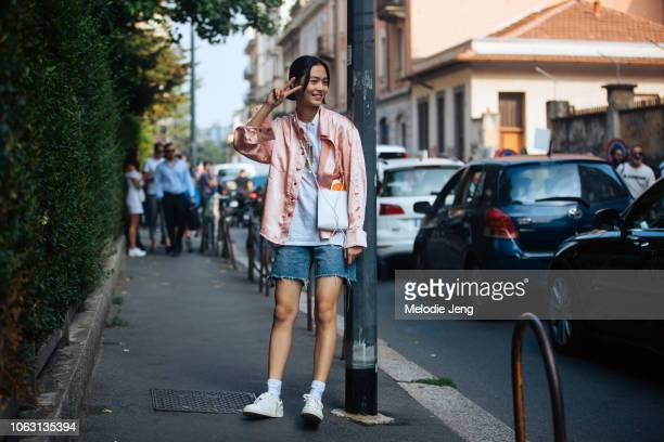 Model Jiali Zhao throws a peace sign and wears a pink shirt white top white Jil Sander bag denim cutoff shorts and white sneakers during Milan...
